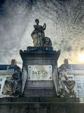Brussels, Belgium Detail of marble statue monument in Martyrs Square against cloudy blue sky. stock photography