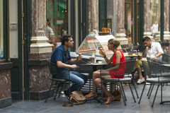 A couple eating an ice cream. BRUSSELS, BELGIUM - JULY 4, 2015: BRUSSELS, BELGIUM - JULY 4, 2015: A couple eating an ice cream at a cafe in the Galeries Royales royalty free stock photography