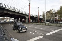 A old beetle car as the only car on a intersection in Brussels with the train bridge of the south train station. Brussels / Belgium - November 25th 2017: a old Royalty Free Stock Photo