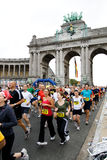 Brussels marathon 2009. BRUSSELS - OCTOBER 4: Participants of Brussels half marathon run through Triumphal arch shortly after start. October 4, 2009, Brussels royalty free stock photo