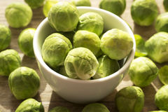 Brussels sprout. In white bowl an scattered on wooden background Stock Photo