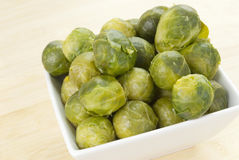 Brussels Sprouts. Boiled brussels Sprouts in a white bowl with a cutting board background. Selective Focus. Shallow DOF. RGB color space. Natural light streaming Royalty Free Stock Photography