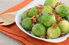 Brussels sprouts with bacon and lemon zest. Steamed brussels sprouts with crisp bacon bits and fresh lemon zest in white serving dish Stock Image