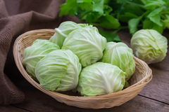 Cabbage in basket on wooden table. Cabbage in wicker basket on wooden table Royalty Free Stock Image
