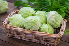 Cabbage in basket on wooden table. Cabbage in wicker basket on wooden table Royalty Free Stock Photography