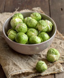 Brussels sprouts in a bowl. On burlap on a wooden table Stock Photo