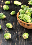 Brussels sprouts in bowl. Fresh brussels sprouts in a bowl and vegetables scattered on the wooden background Royalty Free Stock Photo