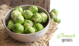 Brussels sprouts in a bowl. On an old wooden table Stock Photos
