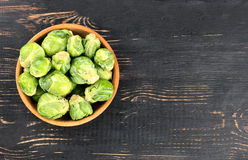 Brussels sprouts in bowl. Raw brussels sprouts in a bowl on blank wooden background Royalty Free Stock Photos