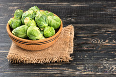 Brussels sprouts in bowl. Bowl with raw brussels sprouts on sackcloth and table Royalty Free Stock Images