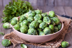 Brussels sprouts in a bowl. On a wooden table Stock Photography