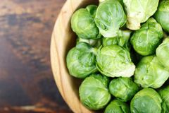 Brussels sprouts closeup. Raw brussels sprouts in a plate on a wooden background, space for text Royalty Free Stock Images