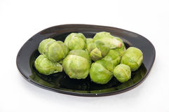 Brussels sprouts on a dark plate on a kitchen tablecloth.  Stock Images