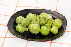 Brussels sprouts on a dark plate on a kitchen tablecloth.  Stock Photo