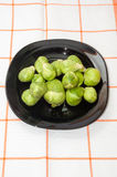 Brussels sprouts on a dark plate on a kitchen tablecloth Stock Photos
