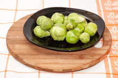 Brussels sprouts on a dark plate on a kitchen wooden board Stock Photos