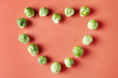 Brussels sprouts heart love shape on red background. Seasonal vegetables in modern style pattern Royalty Free Stock Photo
