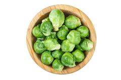 Brussels sprouts isolated. Raw brussels sprouts in a plate on a wooden background, place for text, isolated on white background Royalty Free Stock Photography