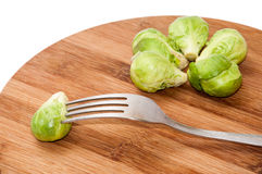 Brussels sprouts on a kitchen board and one pierced with a fork Stock Images