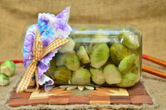 Brussels sprouts. Marinated Brussels sprouts in the winter in a beautiful pot on natural wooden stand Stock Image