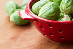 Brussels sprouts in red colander on wooden chopping board Stock Photography