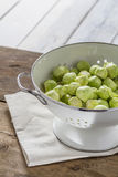 Brussels sprouts in a sieve on a table. Brussels sprouts in a sieve on a wooden table Stock Images