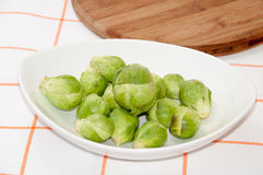 Brussels sprouts in a white bowl on a kitchen table cloth.  Royalty Free Stock Photography