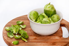 Brussels sprouts in a white bowl on a kitchen wooden board Royalty Free Stock Photography