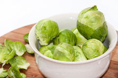 Brussels sprouts in a white bowl on a kitchen wooden board Royalty Free Stock Photo