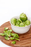 Brussels sprouts in a white bowl on a kitchen wooden board Royalty Free Stock Images