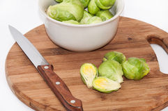 Brussels sprouts in a white bowl on a kitchen wooden board and k Stock Photos