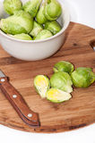 Brussels sprouts in a white bowl on a kitchen wooden board and k Stock Photography