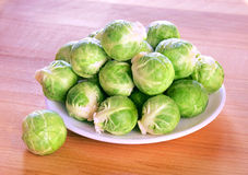 Brussels sprouts on a wooden table. Several heads of fresh wet brussels sprouts on a white plate on a wooden table Royalty Free Stock Image