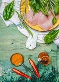 Brust des Huhns mit frischen Bestandteilen für das Kochen auf grünem rustikalem Hintergrund, Draufsicht Lizenzfreies Stockbild