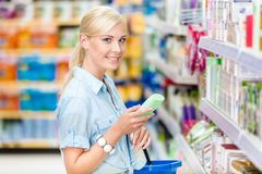 Brustbild des Mädchens am Shop, der Kosmetik wählt Stockfotos