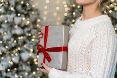 Brustbild des schönen blonden Mädchens, das mit Geschenk in den Händen aufwirft stockfoto