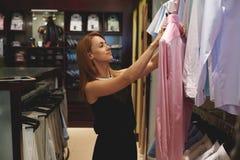 Brustbild eines jungen Schönheitskäufers, der das Hemd der rosa Männer bei der Stellung im modernen Shopinnenraum hält Lizenzfreie Stockfotos