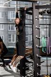 Brutal athletic man dressed in black sorts clothes pulls up on the bar in the gym royalty free stock photos