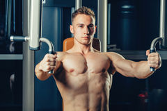Brutal athletic man pumping up muscles on Royalty Free Stock Image