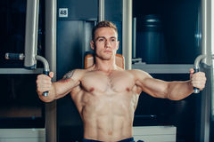 Brutal athletic man pumping up muscles on Royalty Free Stock Photography