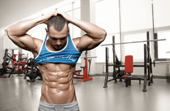 Brutal athletic man taking shirt off on the gym Stock Photo