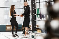 Brutal athletic man and young slender girl dressed in black sorts clothes nice talk in the gym standing next to sports royalty free stock photo