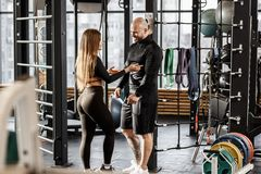 Brutal athletic man and young slender girl dressed in black sorts clothes nice talk in the gym standing next to sports royalty free stock images