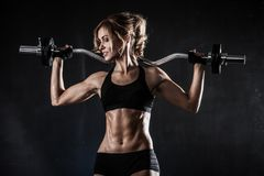 Beautiful athletic woman makes exercises with barbell stock photography