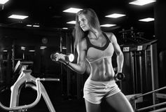 Brutal athletic woman pumping up muscles with dumbbells Stock Image