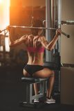 Brutal athletic woman pumping up muscles with Stock Photo