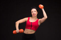 Brutal athletic woman pumping up muscules with dumbbells Stock Image