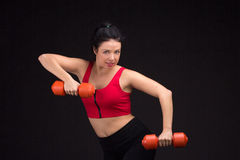 Brutal athletic woman pumping up muscules with dumbbells Royalty Free Stock Photography