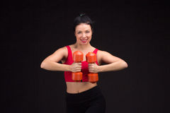 Brutal athletic woman pumping up muscules with dumbbells Royalty Free Stock Photos