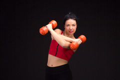 Brutal athletic woman pumping up muscules with dumbbells Royalty Free Stock Photo